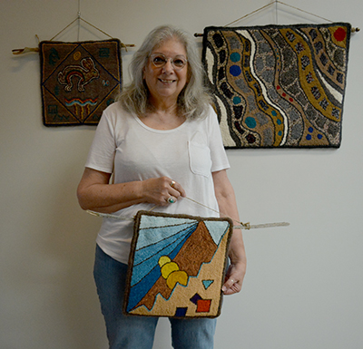 Rug artist Beth Soucie with three of her pieces. Photo by Raquel Hendrickson