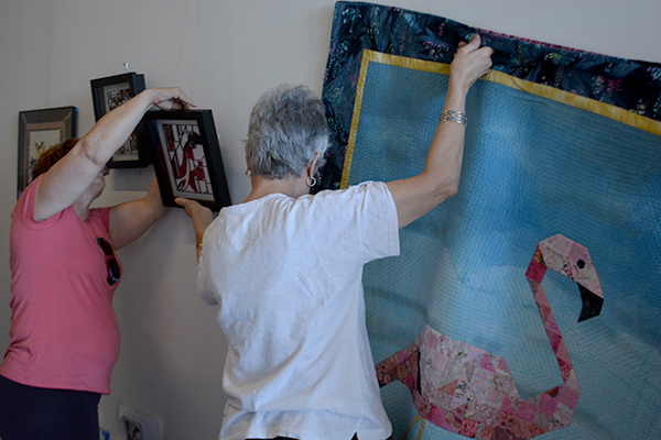 Artists busily hanging art for the gallery at City Hall. Photo by Raquel Hendrickson